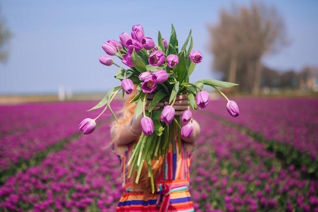チューリップの花の花束とバスケットを持ってドレスを着ている赤い髪の女性