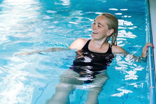 Девушка портрета имея потеху в крытом бассейне в курорте гостиницы.