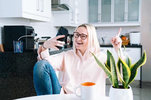 Девушка сидит дома кухня и проведение видеозвонков.