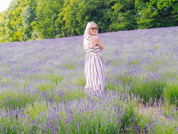 Красивая белокурая женщина в платье сидит между лавандовыми полями в провансе. фиолетовые лавандовые поля цветут в солнечном свете лета. море сирени цветы пейзаж. букет душистых цветов французского прованса