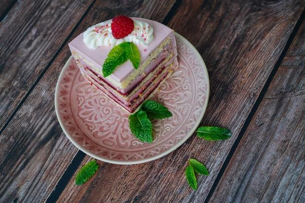 Вкусный кусочек малины многослойный торт на тарелку. малиновый торт подается на десерт на деревянный стол с листьями мяты. вкусный кусочек пирога на тарелку. выпечка и украшение малинового торта