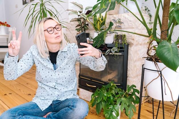家庭の台所に座って、ビデオ通話を保持している幸せな女の子