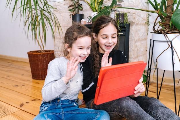 家で座っているとビデオ通話を保持している子供を持つ女性