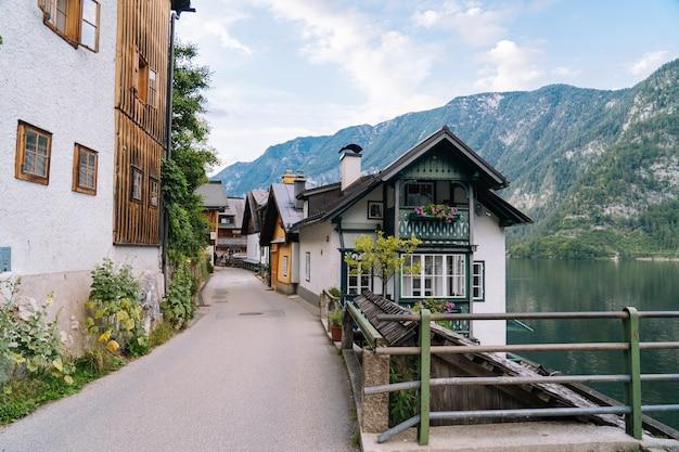 。花とオーストリアアルプスの山の歴史的建造物とカラフルな町。観光客は歴史的な村を歩きます。古いヨーロッパの場所。