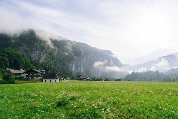 アルプスの朝の牧歌的な教会の風光明媚なパノラマビュー。オーストリアのアルプス地方の美しい霧の朝の風景。オーストリアの霧山、霧、家、緑の牧草地の素晴らしい朝の景色。