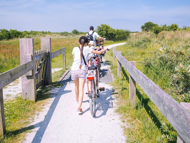 シエルモニコーフ島の砂丘地域の道路を走行する背面のサイクリスト家族。