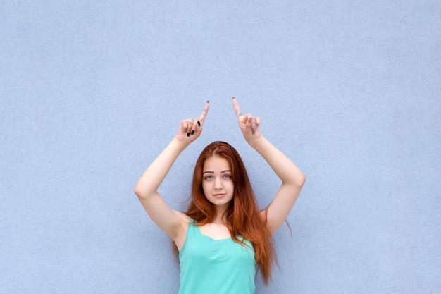 赤い髪の少女を指すとカメラ目線