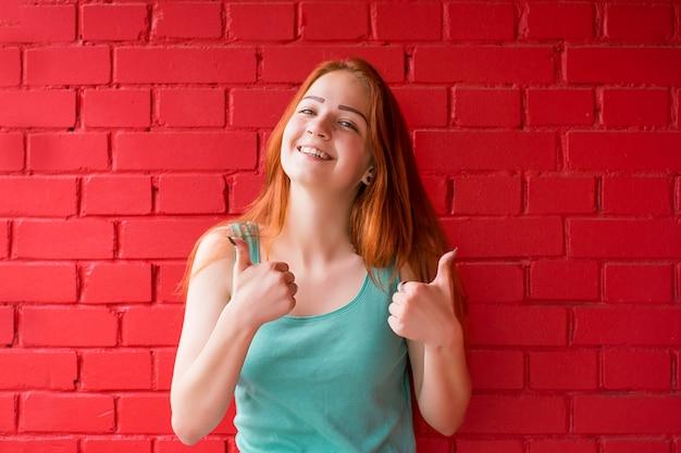 親指を現して幸せな笑みを浮かべて赤髪の女