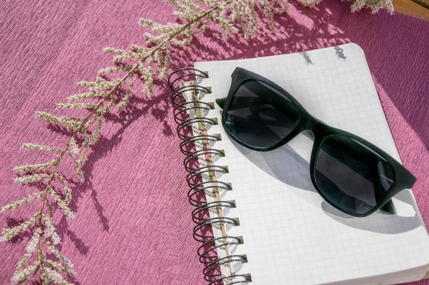 サングラスとピンクの紙に分離されたメモ帳