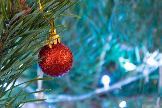 クリスマスボールのクローズアップ。松の木に休日の装飾つまらない。ぼやけた新年照明