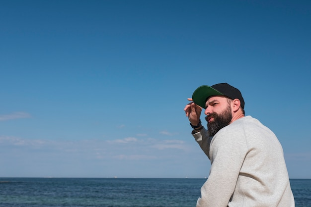 Усы хипстер на пирсе у моря в кепке