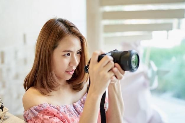 Азиатская молодая красивая девушка с фото в кафе кафе