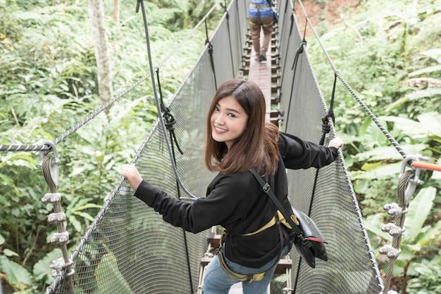 アジアの女性は、ドイ桐の森でぶら下がって橋の上で旅行を楽しむ
