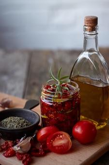 素朴な木製の表面にプロバンスのハーブ、ニンニク、オリーブオイルを加えた天日干しトマト