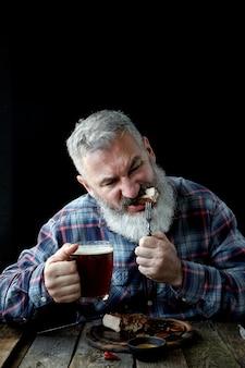 Брутальный седой взрослый мужчина без ума от горчичного стейка и пива