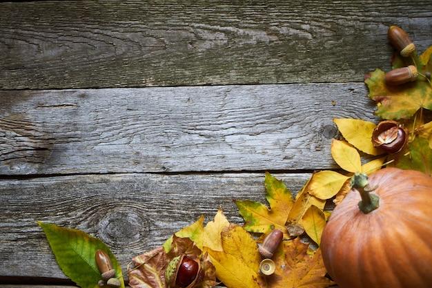 暗い木製の表面、カボチャ、枯れた葉、ドングリ、栗の感謝祭秋の背景