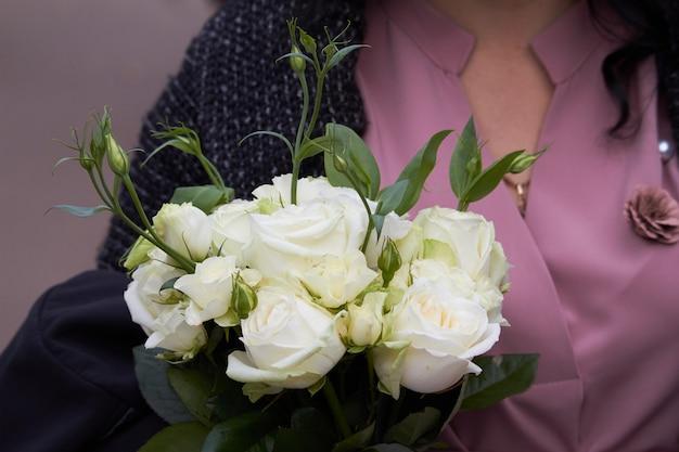 白いアルストロメリアの花束を保持しているクローズアップの女性の手