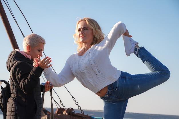 大人の女性同性愛カップルがビーチで古い船でヨガを練習
