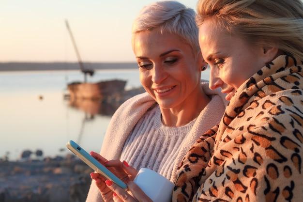 成人女性の同性愛者のカップルは、ビーチでスマートフォンを使用します