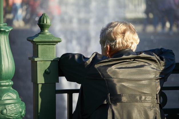 年配の女性が橋の欄干に寄りかかって、噴水を見て