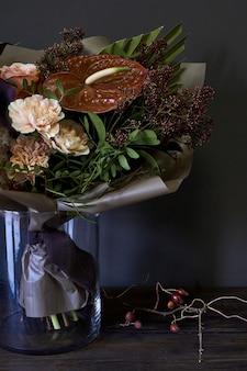 暗い背景にビンテージスタイルで装飾されたガラスの花瓶のクローズアップブーケ