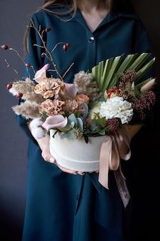 暗い背景にビンテージの花束と箱を保持している女性の手