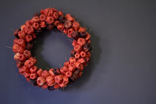 Декоративный венок из красного физалиса на серую стену, селективный фокус