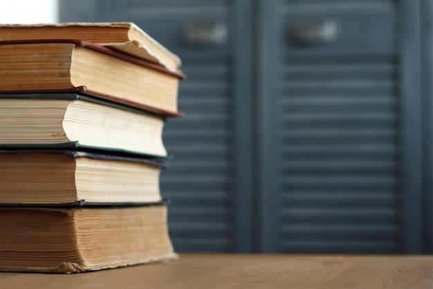 Стек старинных книг крупным планом на деревянной поверхности против серого книжного шкафа