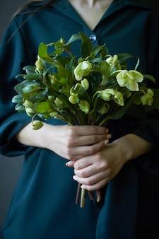 新鮮な咲くヘレボルスの花、セレクティブフォーカスの花束を保持している緑のドレスを着た女性のクローズアップ