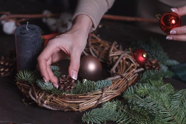モミの枝のクリスマスリースを作る女性の花屋のクローズアップ