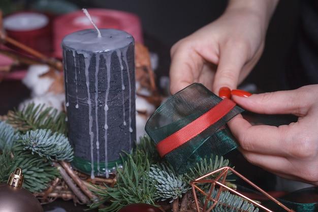 Крупный план женского флориста делает рождественский венок из еловых веток, рождество пузыри и естественный декор