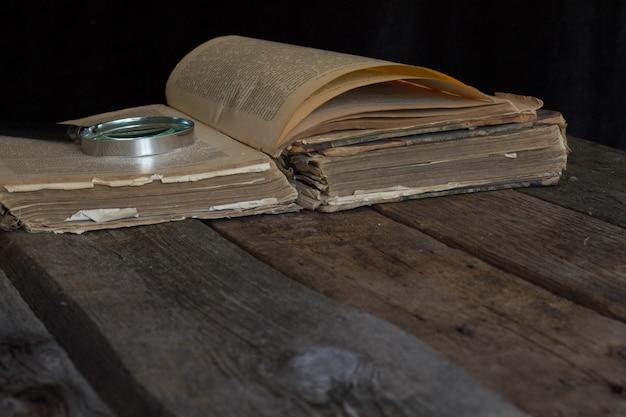 Старая коричневая книга и лупа на деревенской предпосылке.