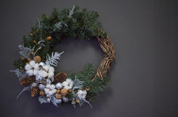 モミの枝、クリスマスボール、天然素材で飾られたブドウのクリスマスリース、