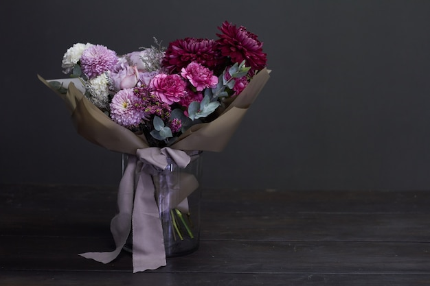 暗闇の中でビンテージスタイルのピンクと紫のトーンブーケ