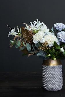 暗闇の中で陶製の花瓶でビンテージスタイルの白いトーンブーケ