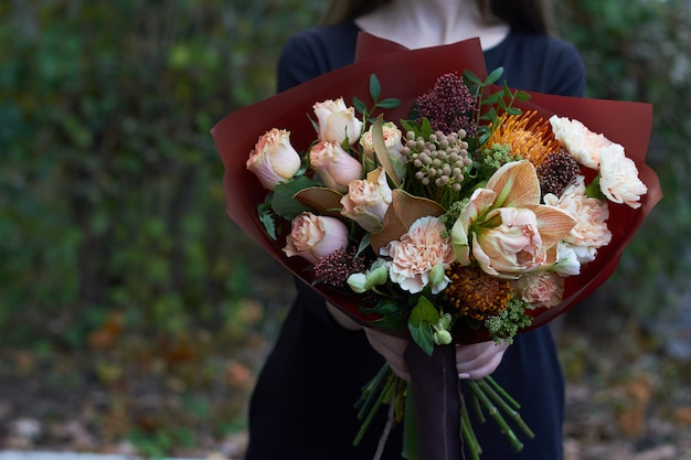 公園の反対側屋外ビンテージスタイルのパステルカラーの花束を持って女の子