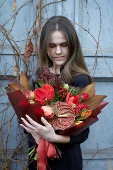女性は、ビンテージスタイルの屋外で赤い色でシックな秋の花束を保持しています
