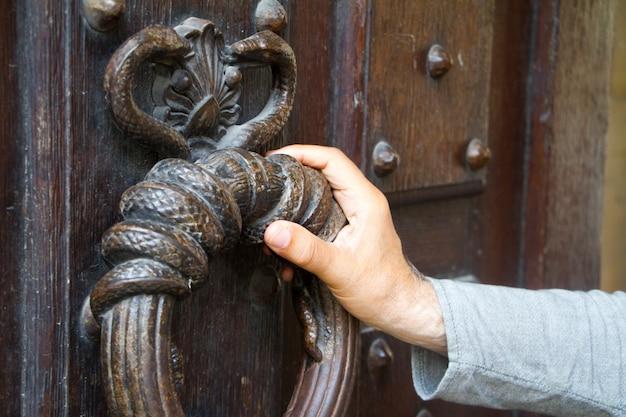 Мужская рука крупным планом на огромном старинном кольце ручки двери