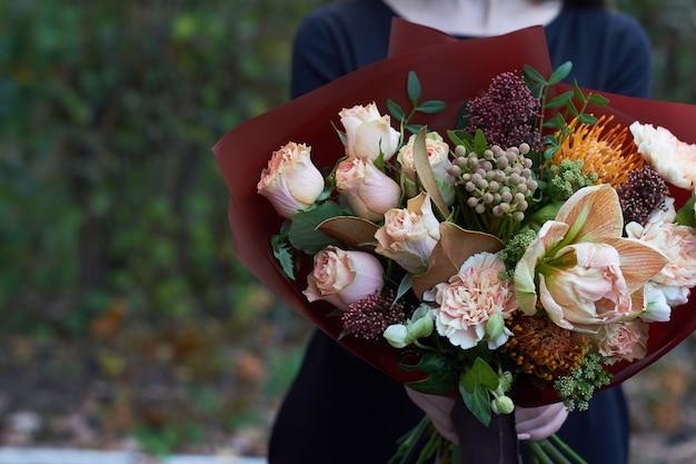 女性は屋外のパステルカラーの花束を保持します