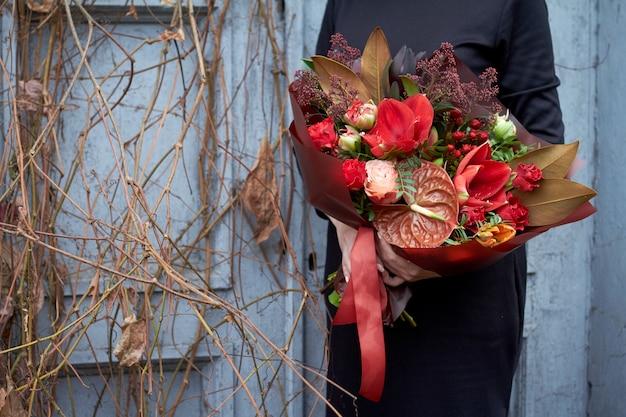 女性は屋外のビンテージスタイルの赤い色でシックな秋の花束を保持しています