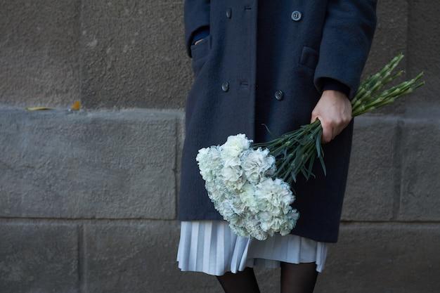 女性は屋外の花の花束を保持します