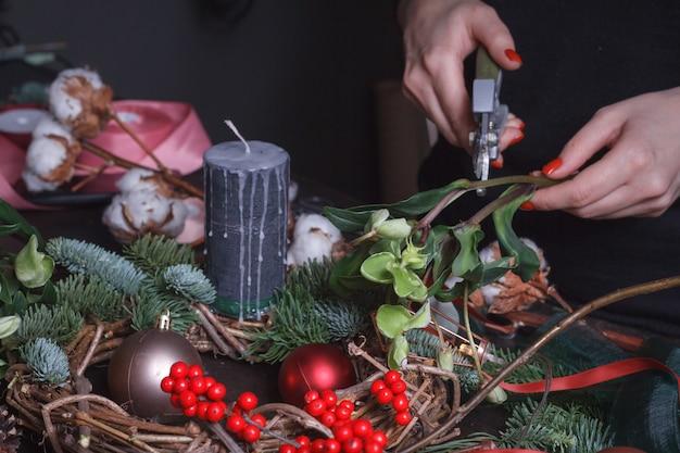 Женский флорист делает рождественский венок из еловых веток