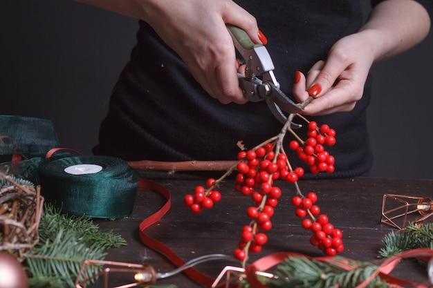 Женский флорист делает рождественский венок из еловых веток и красных ягод