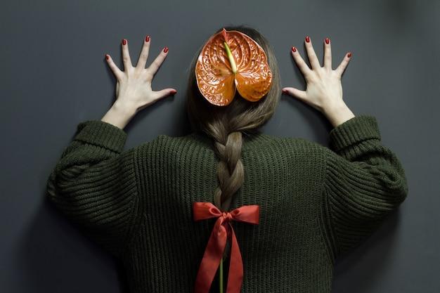 髪を編んだアンスリウムを持つ少女の背面図