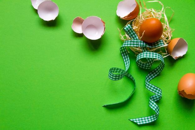 Коричневое куриное яйцо в соломенном гнезде, разбитая яичная скорлупа и зеленая клетчатая лента