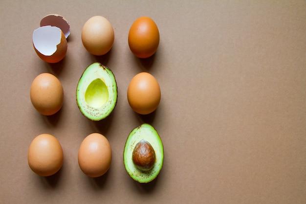 生の半分のアボカド、数個の鶏卵と卵殻