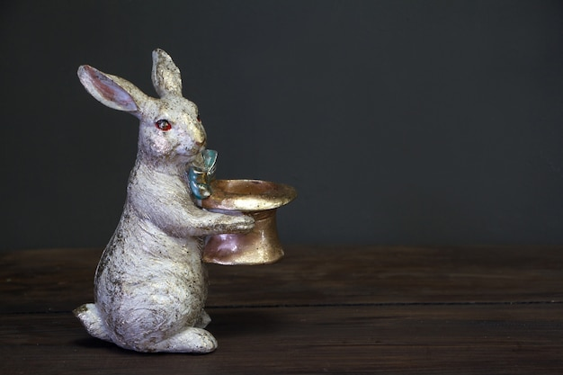 空の帽子、イースターの背景または概念、選択と集中を保持しているイースターのウサギの白い黄金の像のクローズアップ