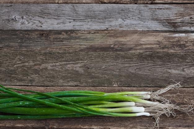 古い大まかな木製の表面、健康的な食事の概念、選択と集中に若い玉ねぎの束
