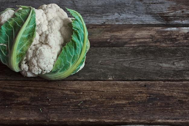 Свежая голова цветной капусты фермера на старой грубой деревянной поверхности, здоровой концепции еды, селективном фокусе