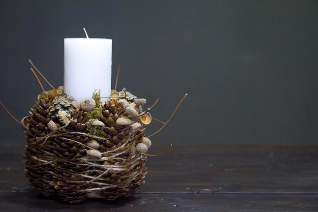 Крупный план зимнего декора с белой свечой на деревянной поверхности, селективный фокус